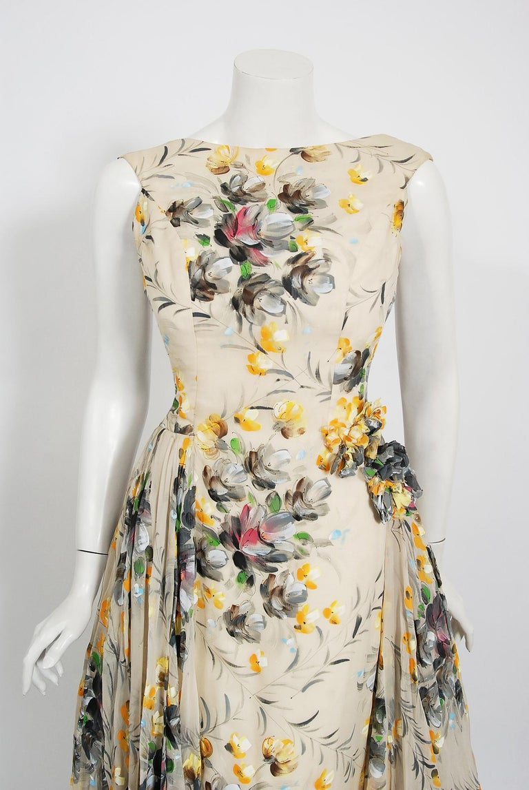 In this gorgeous 1950's hand-painted colorful floral gown, the detailed construction and meticulous attention to detail are comparable to what you will find in modern couture. This captivating garment is fashioned from double layered silk organza in