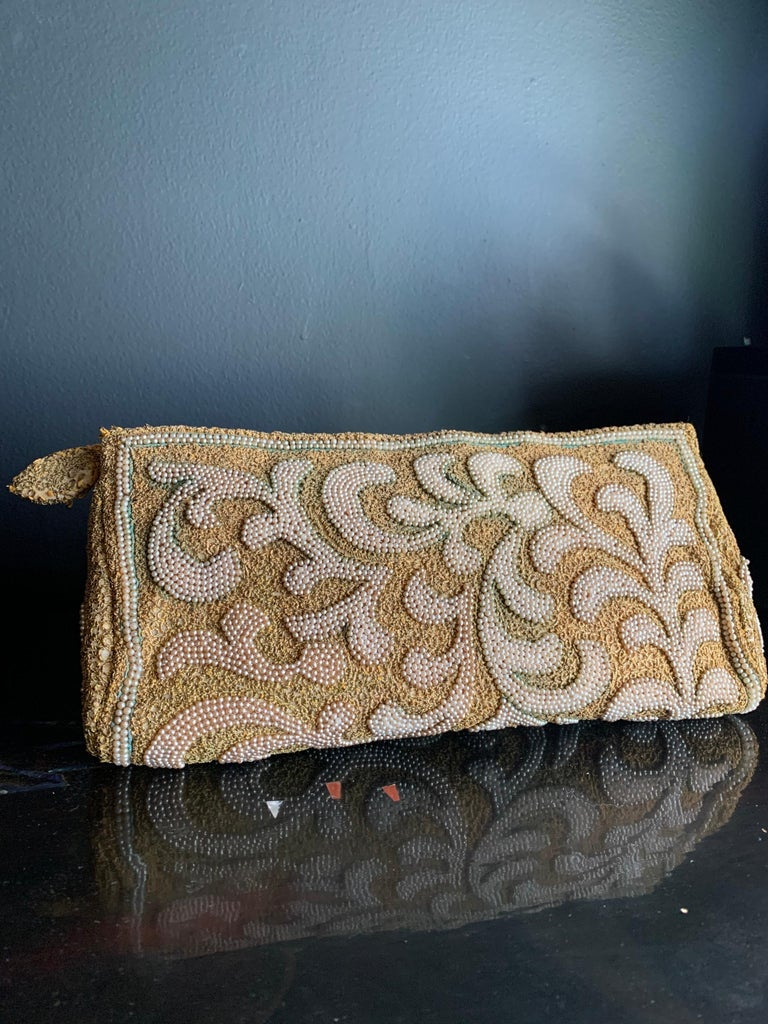 A stunning 1950s Harry Rosenfeld gold filigree lace and faux pearl embroidered evening clutch with embroidered zipper pull. Excellent, clean ivory satin lining with original, chain-tethered coin purse. Some small areas of verdigris on exterior add
