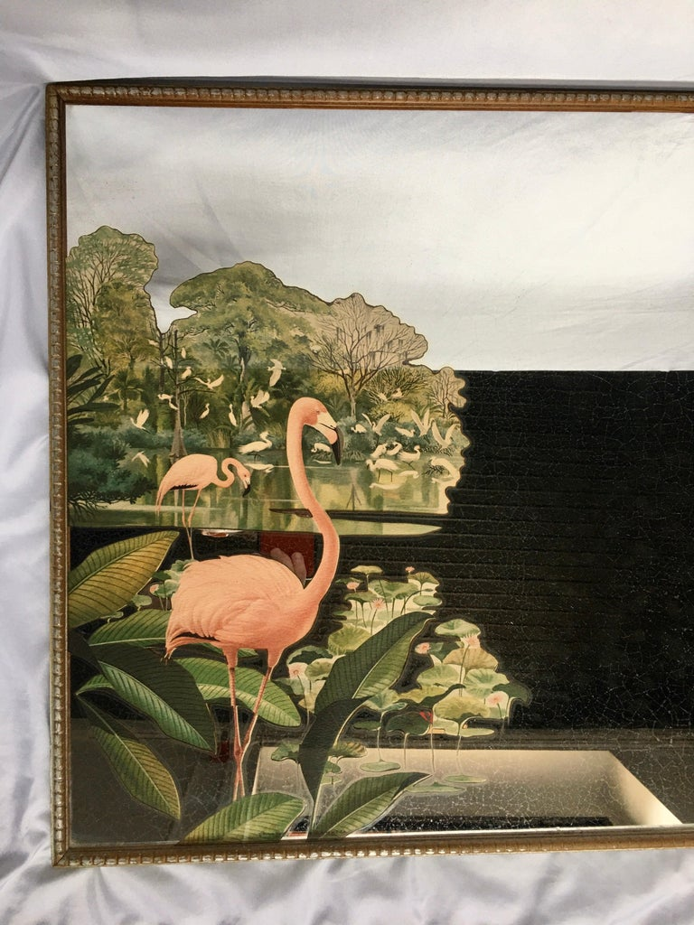 Hollywood Regency decorative wall mirror featuring a painted tropical design of pink flamingos and palm leaves. This midcentury mirrored art piece is framed in a gold/silver tone wood frame, circa mid-20th century. Pair available.