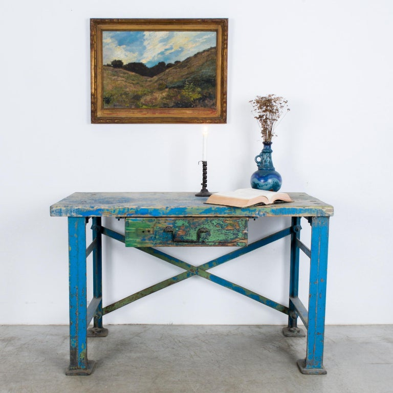 This worktable was made in Central Europe, circa 1950. The table features a wooden tabletop and a drawer. Supported on metal posts with an X-frame back, this sturdy worktable evokes an industrial sensibility. The striking patina of the weathered