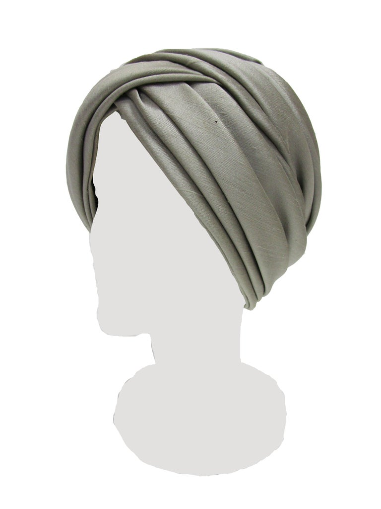 This is a classic turban made by the expert Irene of New York! Grey raw silk wraps around creating this striking turban from the 50s. The neutral color will be easy to wear and agreeable to many garments and styles. The fabric is sturdy and