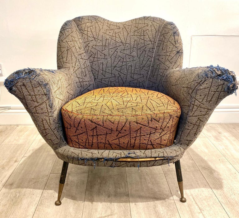 Very cool original 1950s Italian armchair by Poltrona Frau in its original upholstery set on elegant tall and thin black steel legs with brass feet caps.   Really nice and unusual shape with lovely proportions.   Would be perfect for
