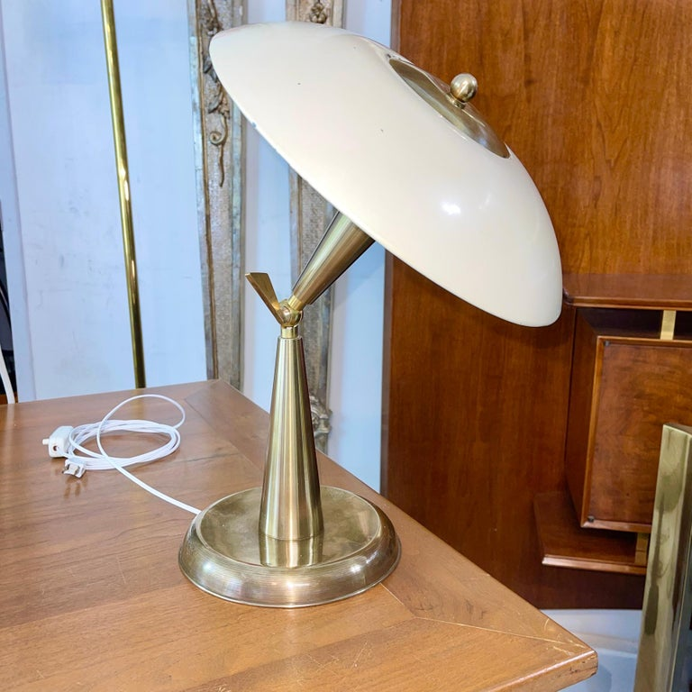 1950's Italian articulating desk lamp made of hefty solid brass and enameled steel reflector. The articulation is controlled by turning the key on the brass ball swivel joint between the double brass cones of the lamp stem. Range of movement is