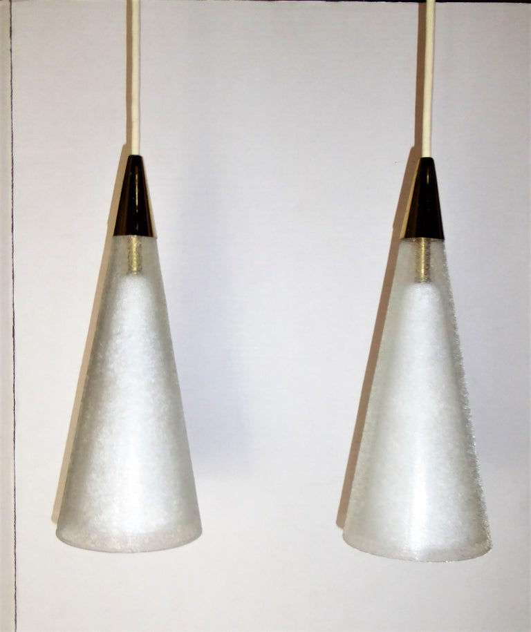 A pair of midcentury Italian pendants of blown glass double cones and brass tips and brass ceiling canopies. Consisting of an inner cone of white milk glass and an outer cone of clear glass with surface glass sugar crystals. Exceptional and luxe.