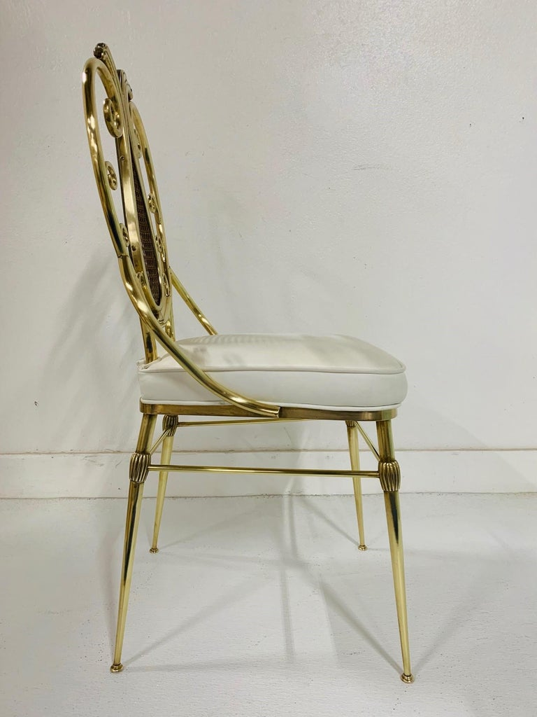 1950s Italian brass Chiavari chair. Decorative brass frame with a hand-caned insert to the back. Has a cushioned vinyl seat.