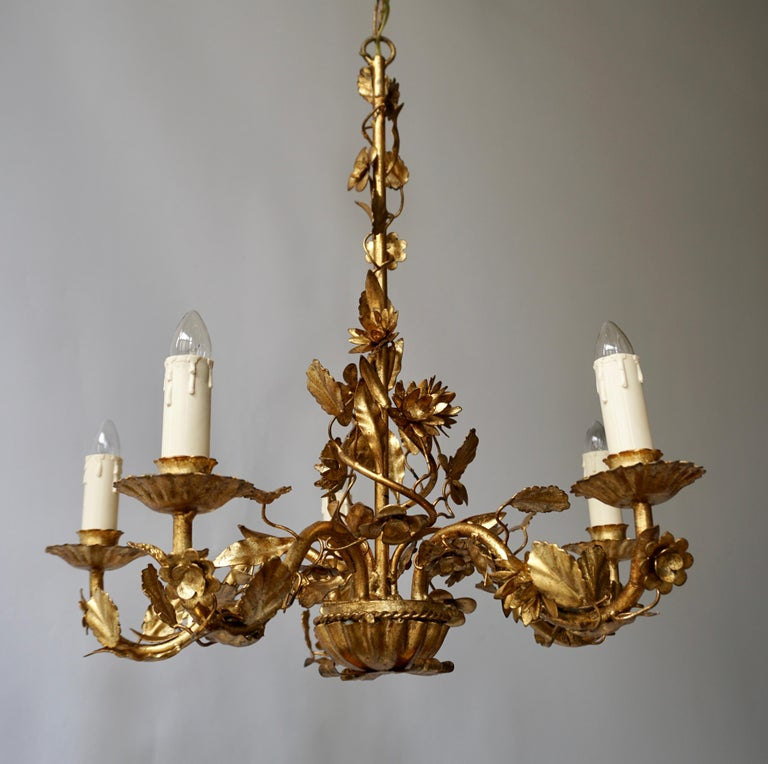 An absolutely stunning vintage chandelier in gilt metal, this was made in Italy and it dates from circa 1950s-1960s. It's of amazing quality with a beautiful floral design. It comes with the original ceiling rosette, seen in the images.