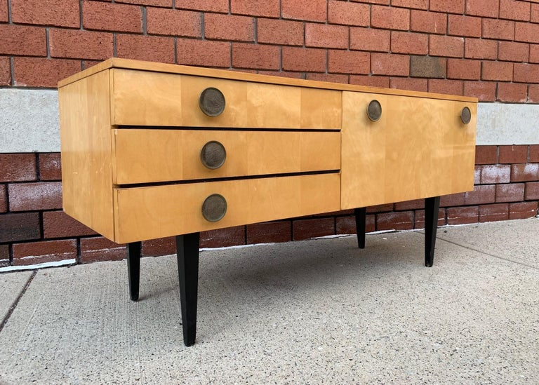1950s Italian low credenza or cabinet. The item is birch, has three pull out / pull-out drawers and a pull down door with storage. Has embossed leather pull handles and wooden black lacquered legs.
