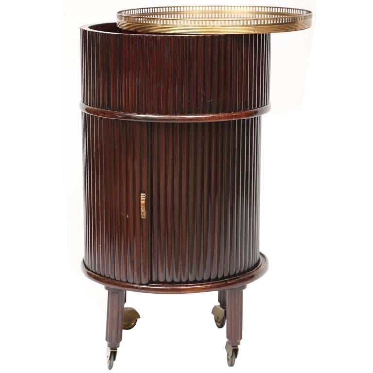 Osvaldo Borsani style 1950s Italian columnar form rolling cocktail cabinet in reeded grizzinato vertical strips of mahogany and matching tambour door which opens to reveal a circular compartment lined with red velvet and a Lazy Susan with slots to
