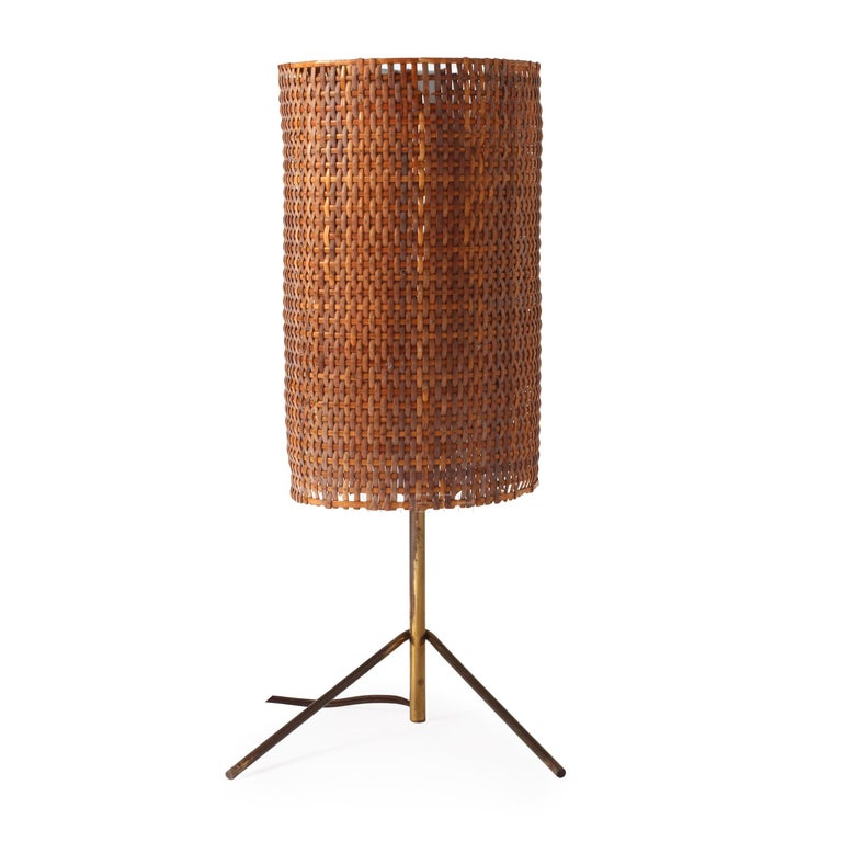 An unusual and expressive table lamp having a spare three-point brass base supporting a lacquered steel and cane shade.