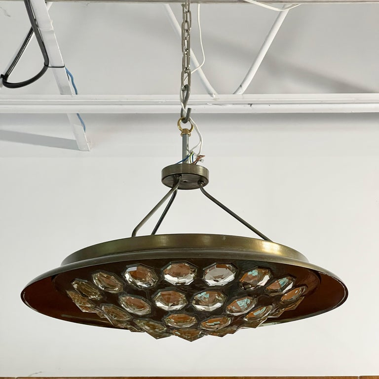 Unique UFO-form pendant light in finely hammered and patinated nickel-plated brass and set with several dozen octagonal cut crystal gems and illuminated from within by six standard size Edison screw cap lightbulbs. From a private estate in Milano