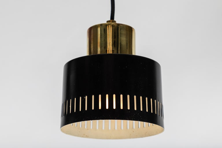 1950s Italian pendant in black and brass attributed to Stilnovo. A quintessentially 1950s Italian design executed in black panted metal and polished brass with a custom fabricated architectural ceiling canopy for mounting over a standard American