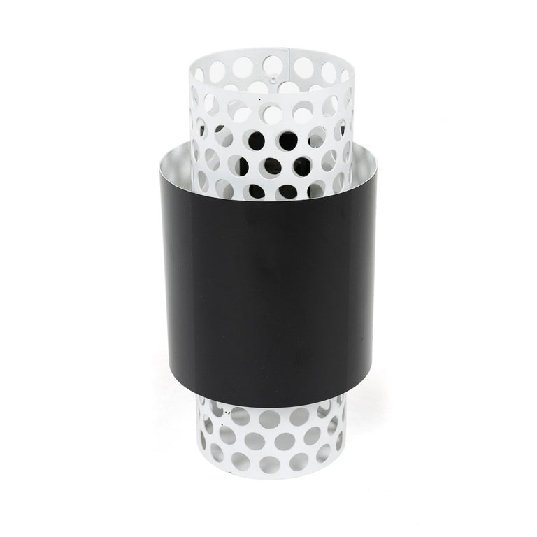 An uncommon wall sconce with a perforated tube core surrounded by a solid tube shade. Original white and black paint. Original Lightolier sticker and stamped