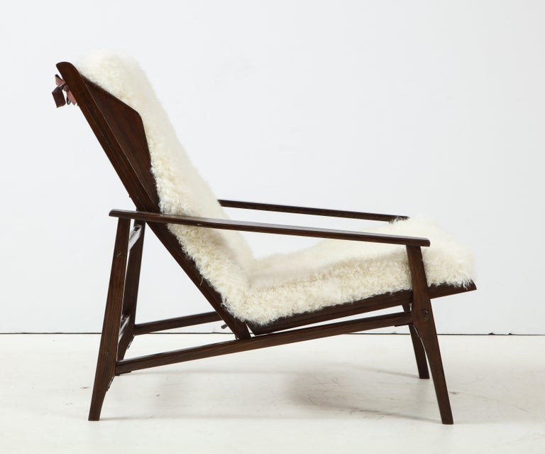 1950s chic Italian reclining lounge chair with stained oak frame and back and seat cushions upholstered in a luxurious white Kalgan lambskin. This lounge chair can be adjusted to different reclining positions. The Kalgan lambskin cushions have