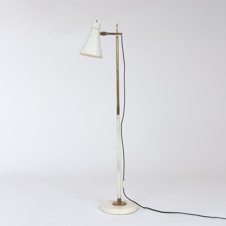 An early telescoping floor / desk lamp with a pivoting cone shaped shade on a brass and enameled steel stem with a ball-and-socket jointed disc base.