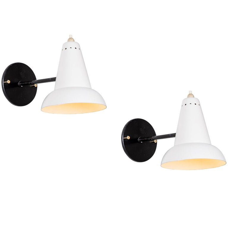 1950s Italian white articulating sconces attributed to Gino Sarfatti. Executed in brass and white painted aluminum. Sconces pivot up/down and left/right on a ball joint. Custom black backplates with brass hardware for hardwiring mounting over