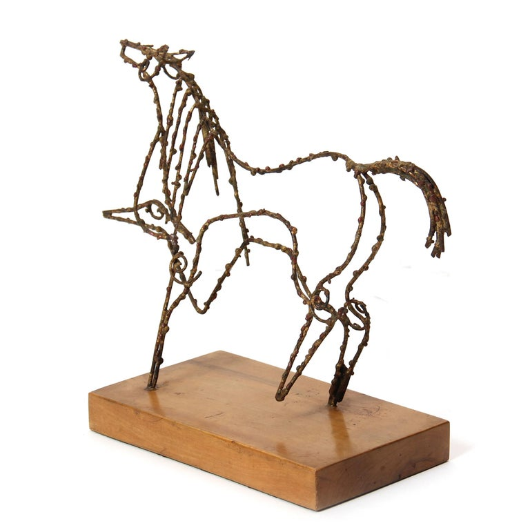 A bronze wire sculpture of a prancing horse on a wooden base.