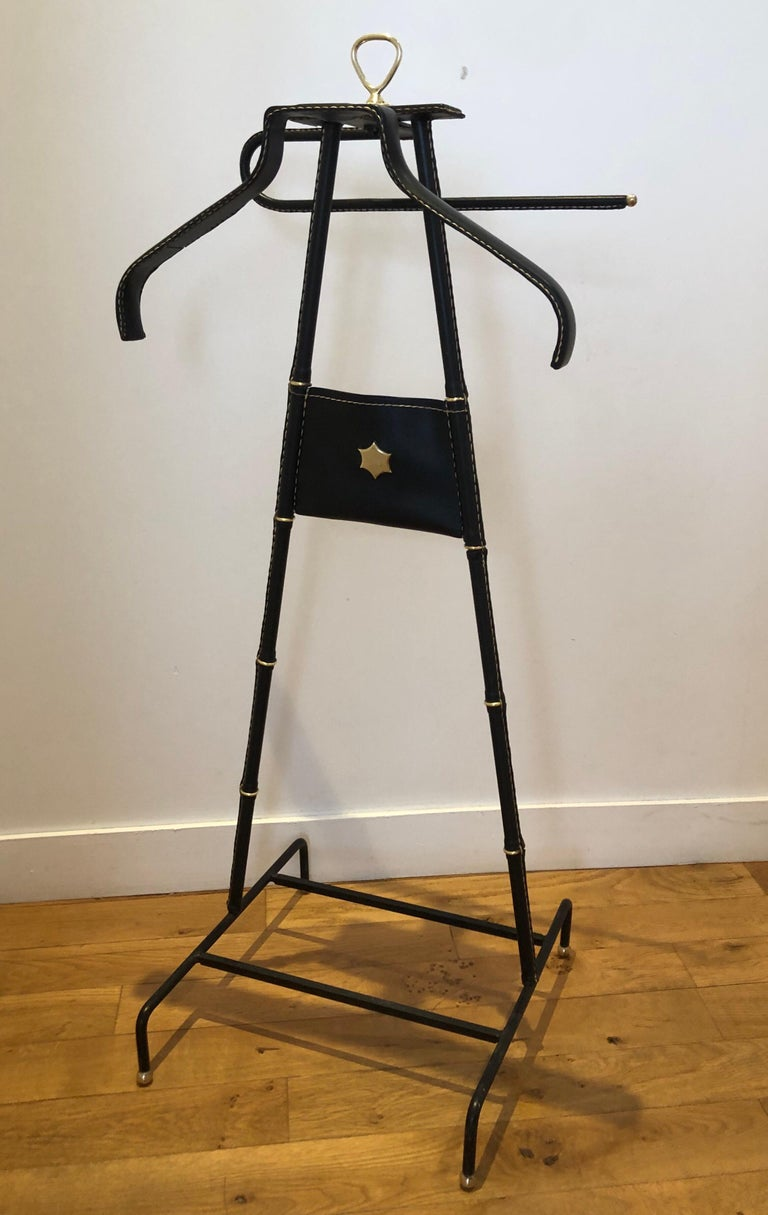 Black faux leather valet by Jacques Adnet decorated with two brass stars: one on the top of the valet and the second on a central pocket. Circa 1950. Great original condition. Measures: Height 105.5 cm    Width 42.5 cm     Depth 40.5 cm.
