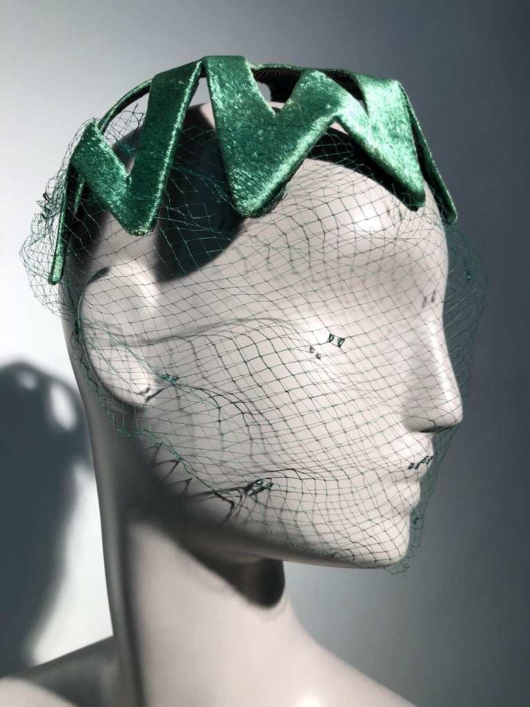 A fabulous 1950s statement hat, most likely from Japan. This emerald green satin stunner is stiffened and molded to fit the front of the head and is lined with a traditional Japanese chrysanthemum pattern. You'll love this bold graphic cut-out