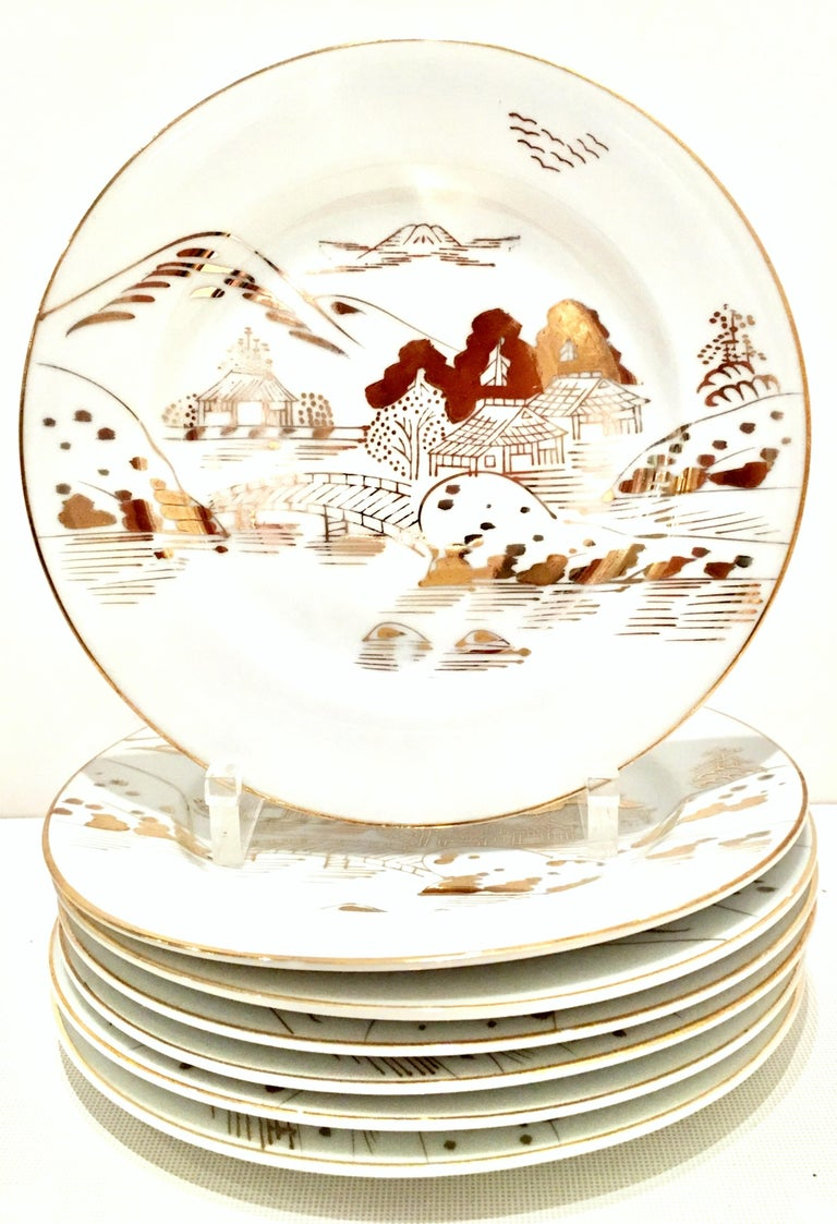 1950s Japanese porcelain and 22-karat gold hand painted dinnerware set of 20 pieces by, Hayasi. This iconic pattern features a bright white ground with painted 22-karat gold detail. Depicts a Mt. Fuji scene with Japanese architectural homes on water