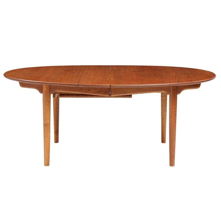 A solid teak oval extension dining table with tapered dowel legs and cloud lift stretchers. Three 25