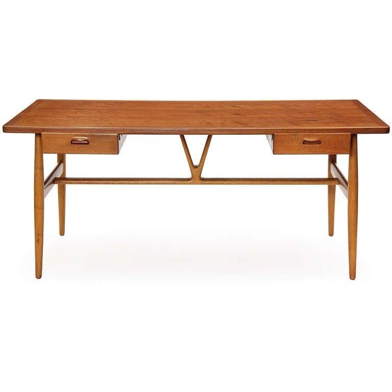 A refined and well proportioned writing desk having a teak top over twin floating drawers, resting on turned oak dowel legs braced by a carved central wishbone-shaped strut.