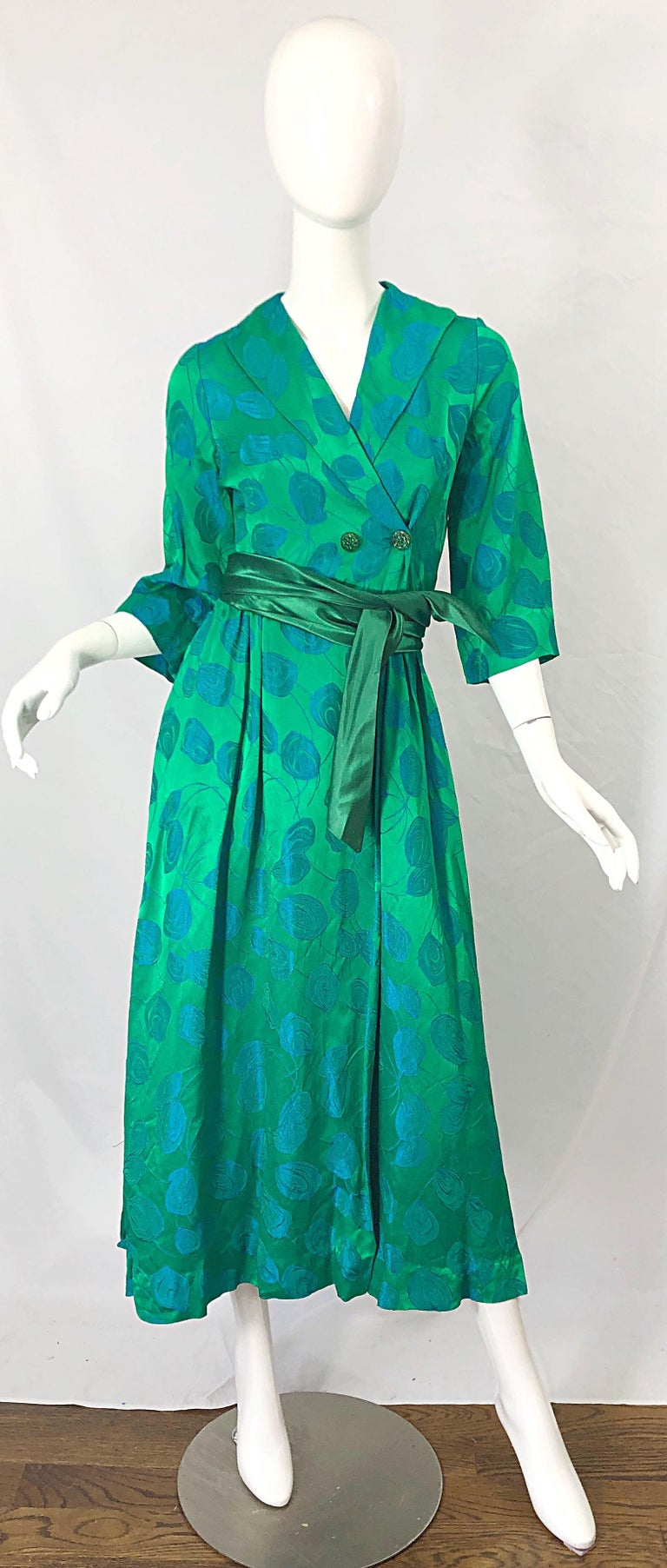 Beautiful vintage 1950s kelly green and blue flower print wrap dress ! Wrap style with interior ties and green rhinestone encrusted buttons. Shawl style collar. Long detachable silk belt. Blue abstract flowers printed throughout. Perfect for any day