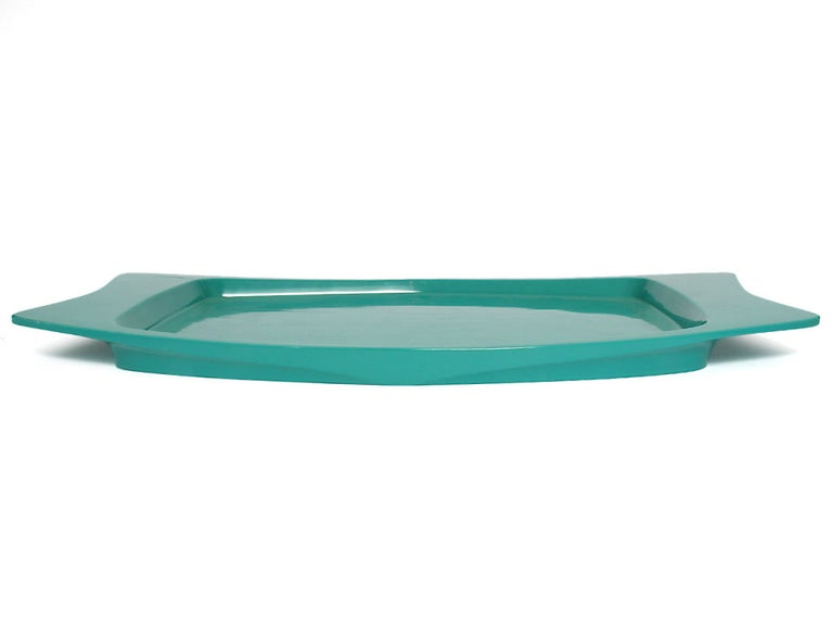 A turquoise lacquered wood tray with broad, indented handles.