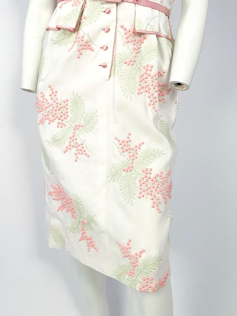 1950s white linen day dress with pink and green raised floral and foliage embroidery, satin covered buttons, piping, lapel, and matching satin belt. Short sleeves are finished with a wide cuff and waist is cinched with faux pocket covers.