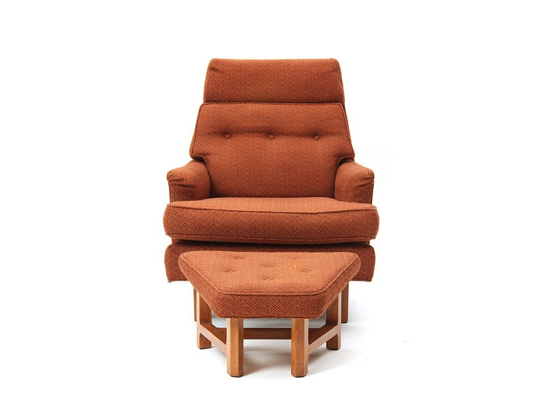 A Mid-Century Modern high-back chair and ottoman set designed by Edward Wormley featuring mahogany bases and original orange upholstery. Made by Dunbar in the USA, circa 1950s.
