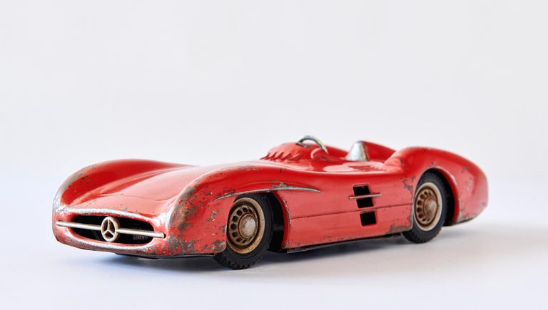This beautiful 1950s metal toy car is an accurately modeled representation of the technological tour-de-force Mercedes-Benz W196 racing car, a masterpiece of streamlining. It was made by JNF -- Johann Neuhierl Fürth -- in the 1950s. Much played with