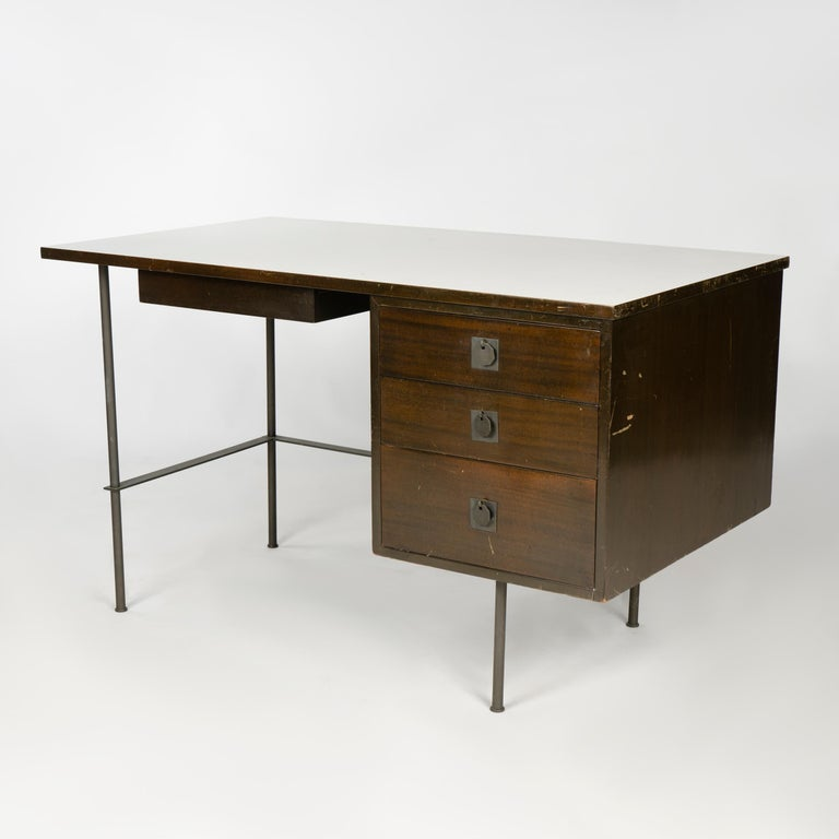 A four-drawer mahogany metaphor desk with solid brass legs and white laminate top. Priced as-is.