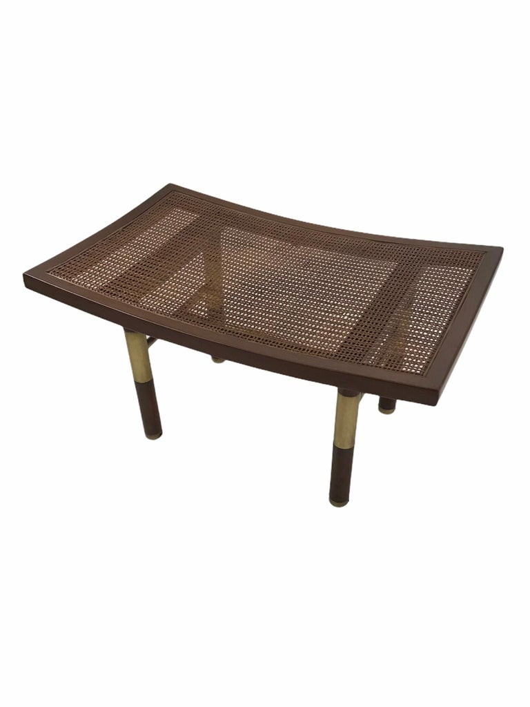 From the 1950s and Michael Taylor, this Far East Collection Bench has a caned top and a pagoda form with turned up ends with brass stretchers and feet. All original, it has been refinished. Some imperfections in the original caning (see pics). Baker