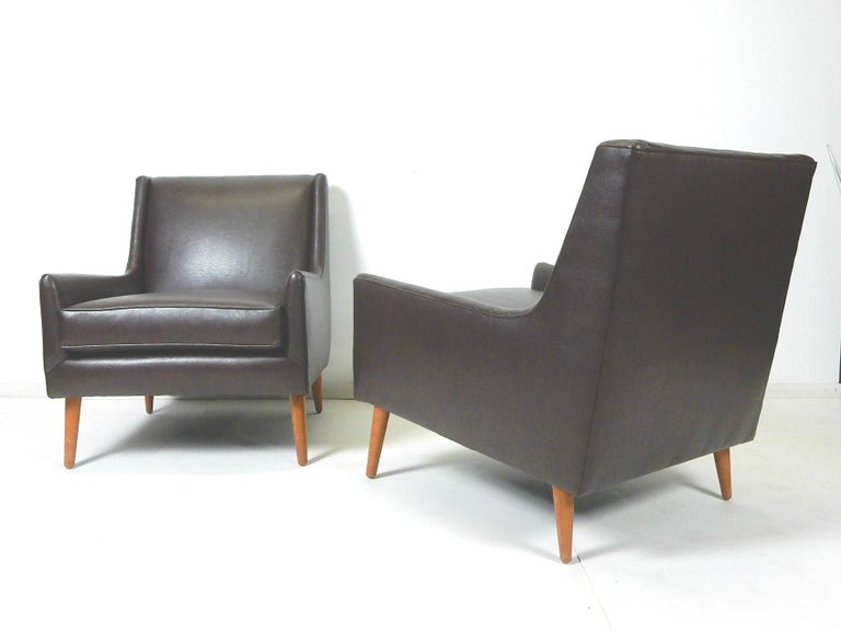 Incredible pair of 1950s Mid-Century Modern lounge chairs that are newly upholstered in Fine butter soft chocolate brown faux leather. They are in the style of Edward Wormley. Not marked or signed. Extraordinary quality chairs that are very plush
