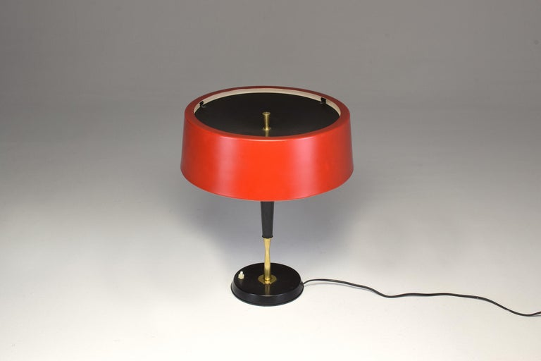 A Mid-Century Modern vintage table lamp or desk lamp by Italian designer Oscar Torlasco for the prestigious Italian lighting manufacturer Lumi.  This tall rare statement piece is composed of a shade in elegant red and a structure of both lacquered