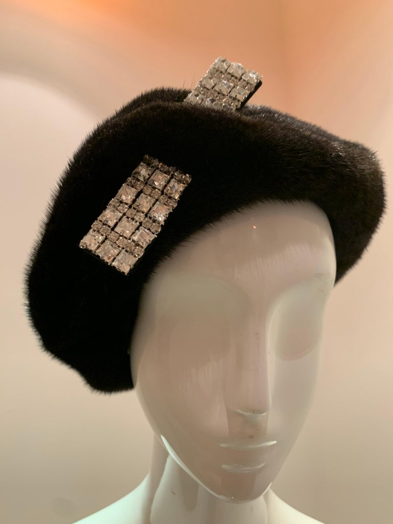 A 1950s mink beret with a stunning rhinestone accent piece that appears to pierce the crown.
