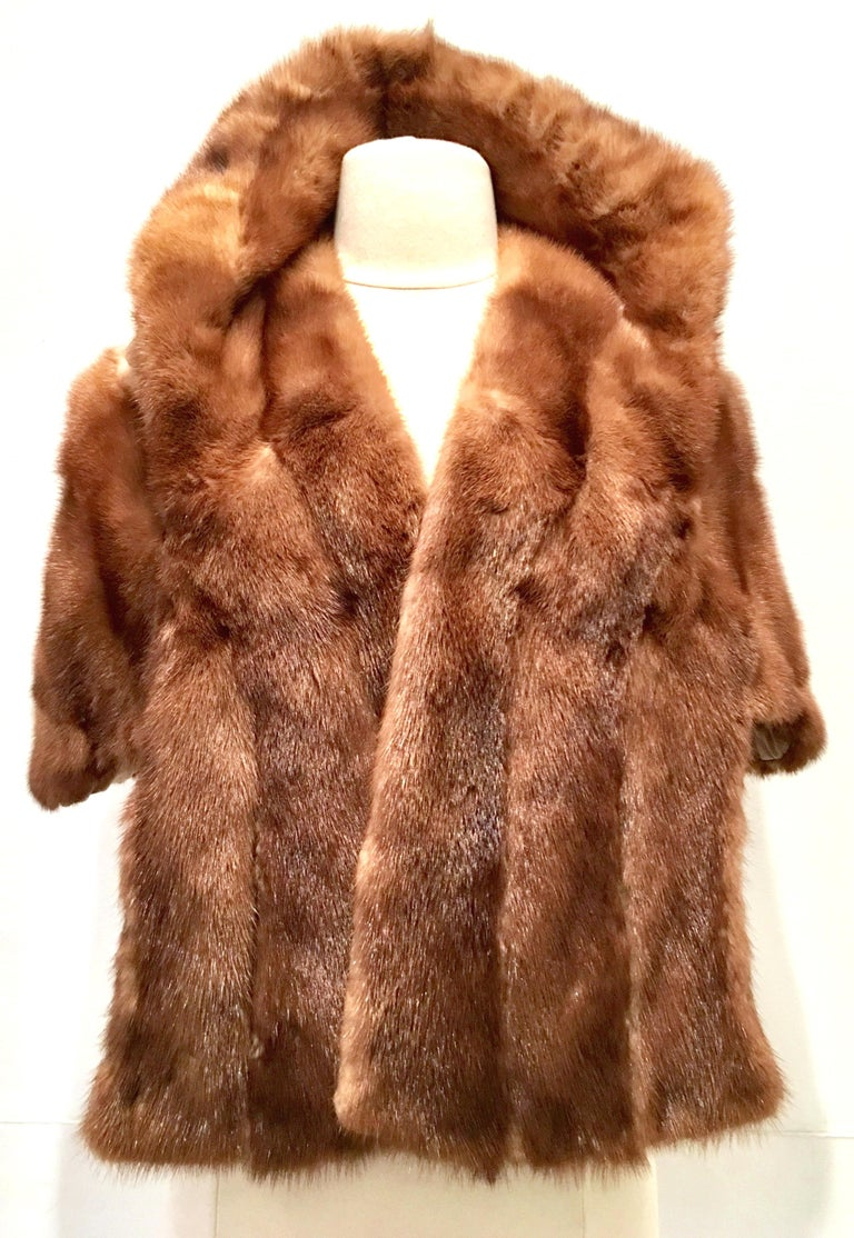 1950'S Mink Fur Capelet By, Lloyd's Fur-Denver. This soft and brilliant brown mink capelet features two side pockets with a roll over adjustable petal hem detail collar. Fully lined and maintains the original furrier label at the interior neck. One