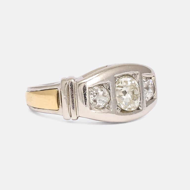 An incredible modernist diamond three-stone ring dating from the 1950s. It's crafted in platinum, with a contrasting 18k gold band around the outer shank, and set with just over 1.30 carats of antique cushion cut diamonds. It's heavy and substantial