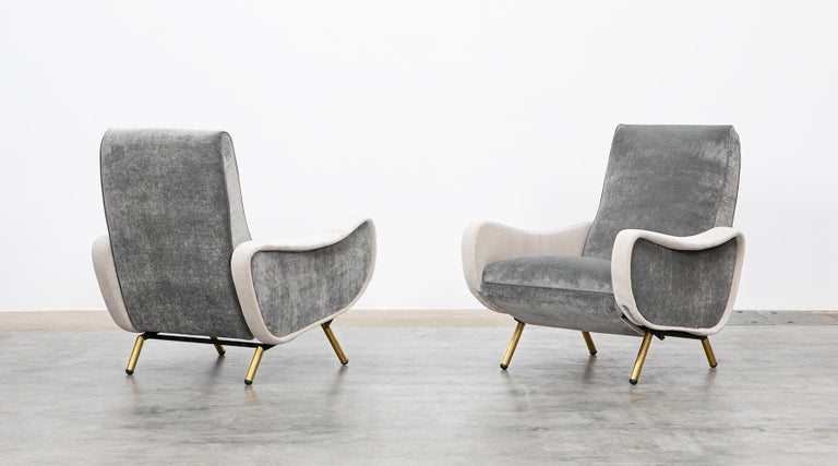 This beautiful couple of lounge chairs designed by Marco Zanuso comes on four brass legs. The seat and the back of the chairs are covered with two different tones in grey and high-quality fabric. The chairs provide exquisitely comfortable seating