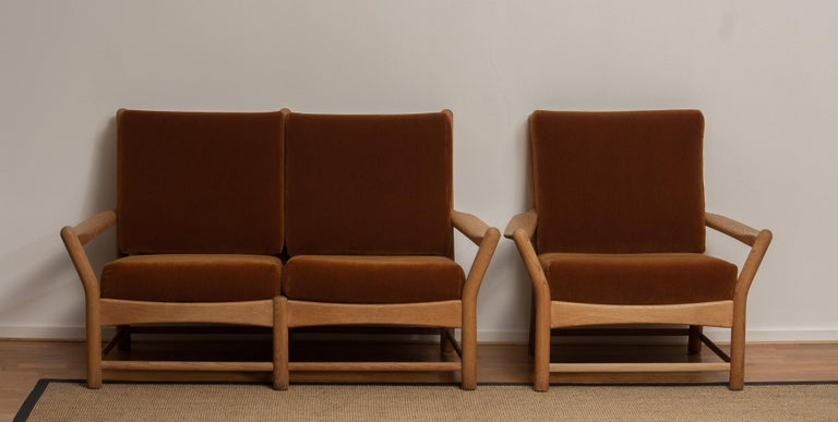 Beautiful two-seats sofa and chair made in Denmark. This lounge set is made of oakwood with brown velvet cushions. It is in a very nice condition. Period 1950s.