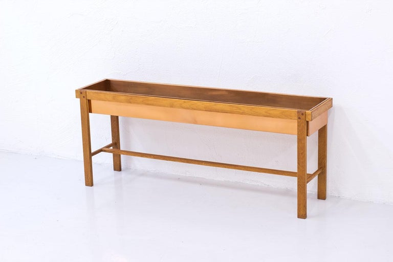 Long flower table, from unknown maker and designer.  Most likely made in Sweden during the 1960s. Solid oak base with copper box. Nice joinery details.