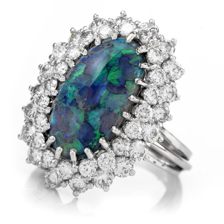 This cosmic opal and diamond ring is crafted in 14-karat white gold, weighing 8.4 grams and measuring 25mm x 12mm high. Showcasing a prominent oval shaped, prong-set opal weighing approximately 3.83 carats. Surrounded by a double halo of 40