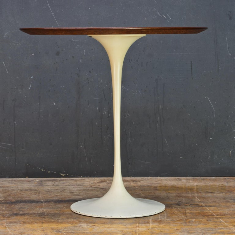 Early 1950s 'Madison Avenue' production Knoll side table. Nice active walnut grain. Please note: There are two (set) screws in base, right at underside of wooden tabletop, not sure what that is, looks factory, possibly a Knoll repair, and