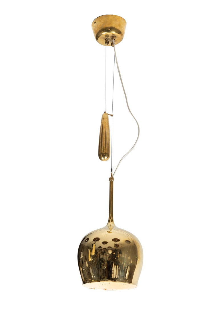 1950s Paavo Tynell A1957 counterweight pendant. This rare and exceptionally refined ceiling light is executed in brass, and can be raised and lowered using its ingenious counterweight and pulley system. Manufactured by Taito Oy in the early 1950s,