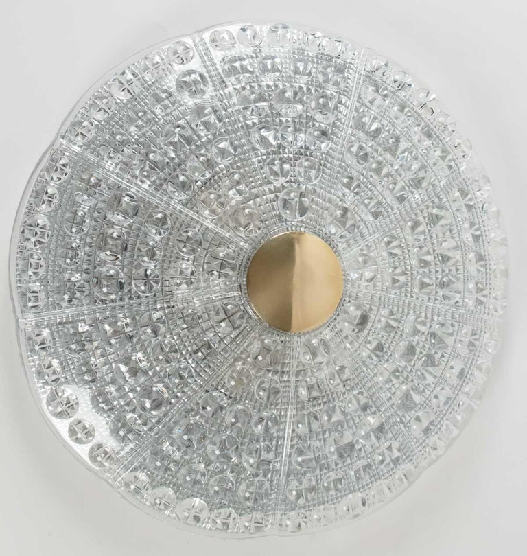 The shades of 40 centimeters of diameter are made of pressed glass with a pattern of blobs and facettes, adorned ay his center by a round piece of brass. Each light contain 6 bulbs.