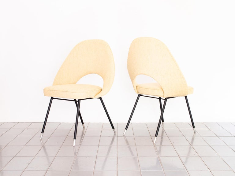 Graceful pair of armchairs upholstered in deliciously soft cream bouclé. Aluminum feet create an interesting effect with the matte black legs.