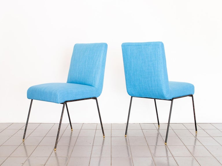 These two 1950's chairs in wrought iron and blue linen fabric are super hard to find and extremely comfortable. Designed by Abraham Palatnik and produced by Arte Viva, they have beautiful brass spheres as feet.   Reupholstered in 100% cotton blue