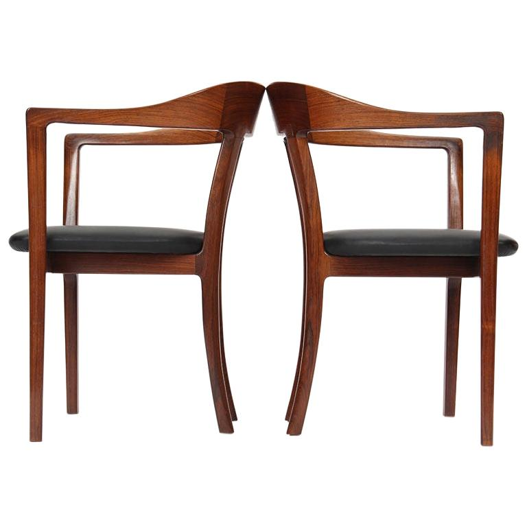 A pair of rosewood hump back arm chairs with black leather upholstery. Designed by Ole Wanscher and Manufactured in 1958 by A.J. Iversen. Fully restored by the Wyeth Workshop.