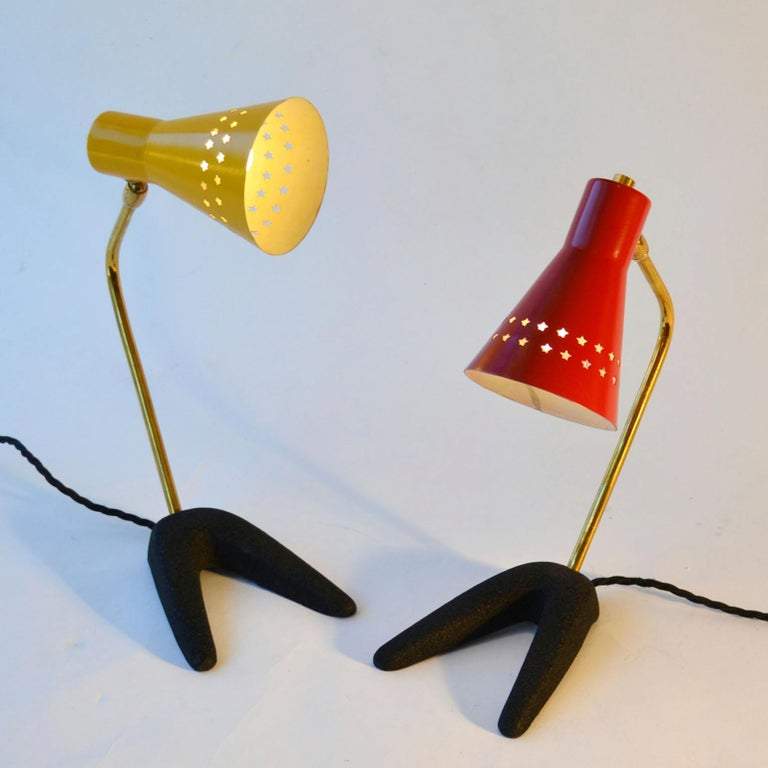 Pair of small table or bedside lamps on crow-feet, one with red and one yellow adjustable metal shade perforated with star-shapes and articulated brass arms. They are attributed to Jean Boris Lacroix, France. The shades are in their original colour
