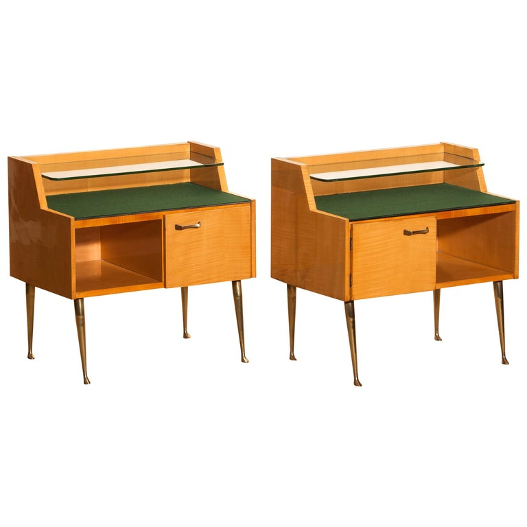 Beautiful set of two Italian midcentury bedside tables in maple with brass legs and brass handle designed by Paolo Buffa, Italy, 1950s. Both are in good condition. The top is covered with green felt and In addition, there's a smaller glass shelf