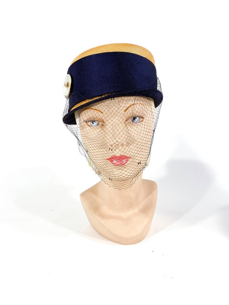1950s natural panama woven modified pill box hat with a side brim, navy edging, a wide asymmetrical band. The band is sculpted with a hand cut abalone and jeweled button. The full-face veil is very dark navy blue and has a tie back function to